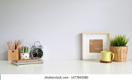 Copy space workspace with photo frame, coffee, plant decoration, pencil on office desk.
