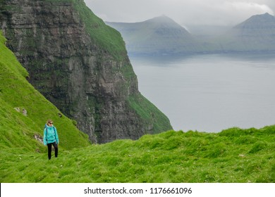 COPY SPACE: Young woman hiking up a grassy hill with a perfect view of the Scandinavian seaside with grassy mainland and tranquil deep blue ocean. Female hiker on awesome vacation in Faroe Islands.