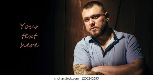 Copy space , your text here ,brutal bearded man with a tattoo on his arm, portrait of a man in dramatic light against a brown wooden wall, attractive bearded male with tattoo on arm dressed in a shirt