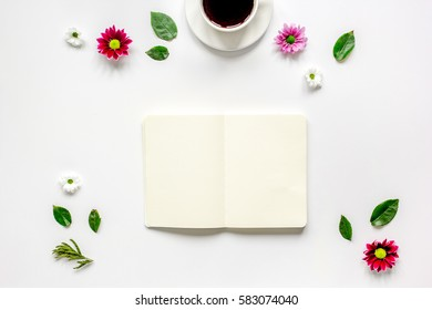 Copybook, americano and flowers on white table top view mock-up