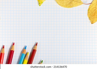 Copybook with colored pencils and autumn leaves.
