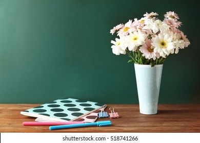 Copybooks and flowers on teacher's desk