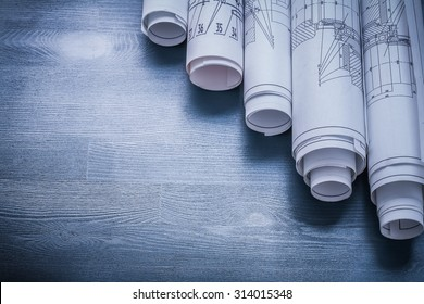copyspace image rolls of blueprints on blue board.