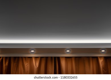 Copyspace on the celling framed by three lights and part of curtains