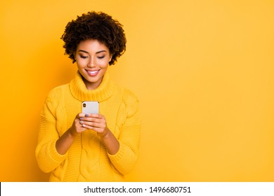Copyspace photo of cheerful cute charming girlfriend browsing through her smartphone wearing pullover addicted to social media isolated with vibrant color background