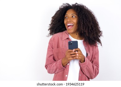 Copyspace photo of young beautiful African American woman wearing pink jacket against white wall stupor with something occurring in social media