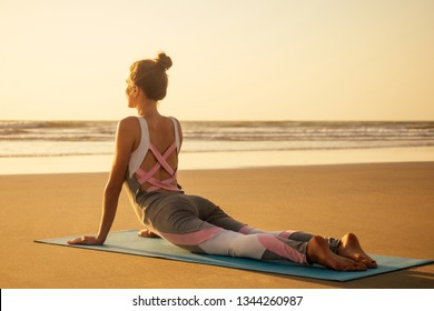 copyspace woman doing yoga performing asanas and enjoying life at sunset on the beach sea copy space