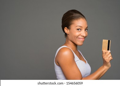 Copy-spaced image of a lovely black woman with a credit card isolated on grey