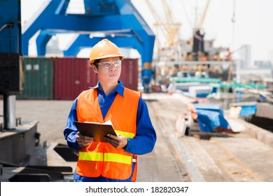 Copy-spaced image of a port superintendent with clipboard controlling the working process in the seaport