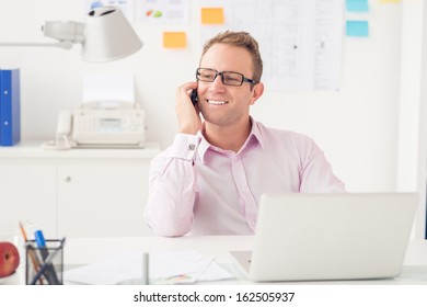 Copy-spaced image of a young businessman talking by phone at the workplace