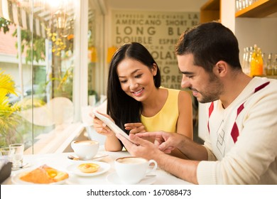 Copy-spaced image of a young couple networking while having breakfast at a cafe