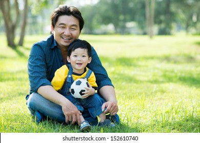 Copy-spaced portrait of a father and his son sitting on the ground in the park