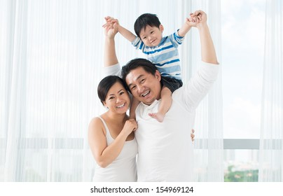 Copy-spaced portrait of a funny family with a cute little boy smiling and looking at camera