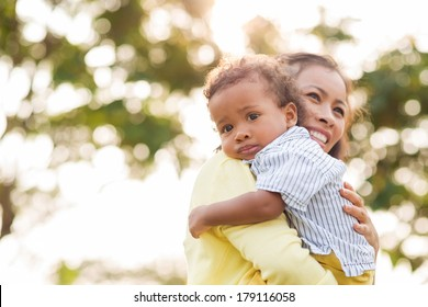 Copy-spaced portrait of a little boy looking at camera while his mother bonding him on the foreground