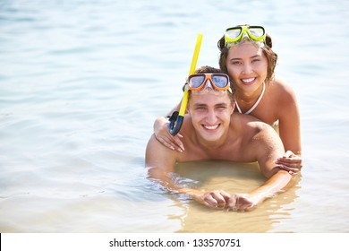 Copy-spaced portrait of smiling young people in scuba masks lying in water