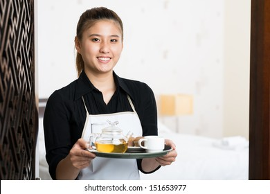 Copy-spaced portrait of a young waitress with prepared breakfast on the tray