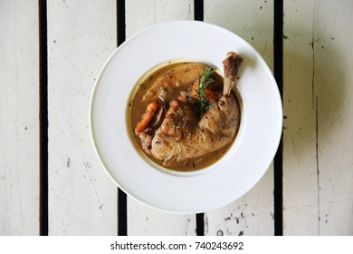 Coq au vin, chicken stewed in red wine with carrots and potatoes on wood background ,  French foods