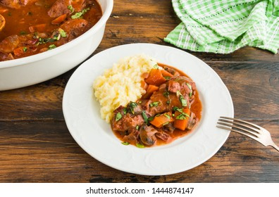Coq au Vin, traditional French recipe of chicken braised in red wine with carrot and mushrooms. Served with mashed potatoes. White casserole and plate on wooden table