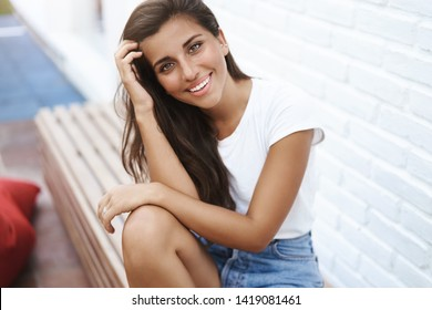 Coquettish alluring modern young hispanic woman dating boyfriend sit park bench near brick white wall talking flirty smiling camera touch hair tilting head cute grinning positive, have fun
