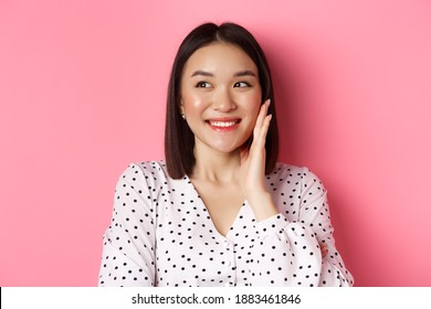 Coquettish asian woman in blushing, touching cheek and looking left amused, standing over pink background