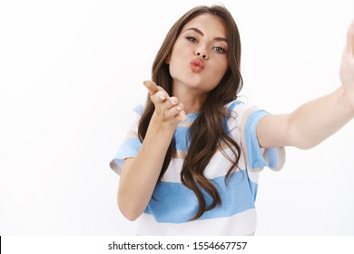 Coquettish glamour young modern woman send selfie boyfriend, blowing air kiss at camera, pouting hold hand near folded lips give muah show sensuality and flirt, white background