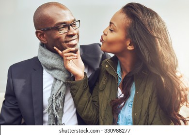 Coquettish young African American woman on a date with a handsome man playfully puckering up her lips for a kiss