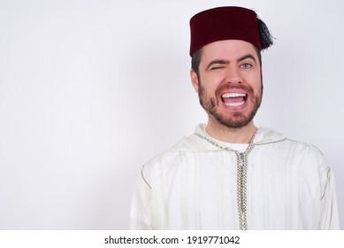Coquettish young handsome Caucasian man wearing Arab djellaba and Fez hat over white wall smiling happily, blinking at camera in a playful manner, flirting with you.