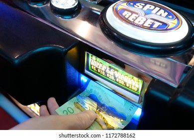 Coquitlam, BC, Canada - June 12, 2018 : Motion of woman inserts money on slot machine inside Casino