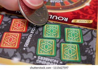 Coquitlam BC Canada - June 16, 2018 : Woman scratching lottery ticket. The British Columbia Lottery Corporation has provided government sanctioned lottery games in BC since 1985.
