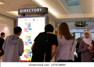 Coquitlam, BC, Canada - March 31, 2019 : Motion of woman checking store position in front of directory sign inside shopping mall