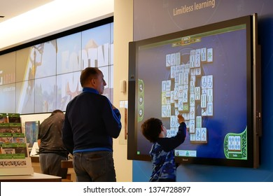 Coquitlam, BC, Canada - March 31, 2019 : Motion of father and children playing xbox game on tv screen at Microsoft store
