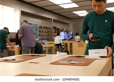 Coquitlam, BC, Canada - May 03, 2018 : Worker scanning gamepad for customer inside Apple store at Coquitlam shopping mall