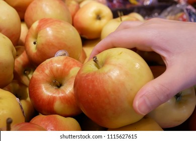 Coquitlam, BC, Canada - May 14, 2018 : Motion of woman's hand picking organic ambrosia apple inside supermarket