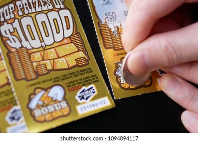Coquitlam BC Canada - May 15, 2018 : Woman scratching lottery ticket on bonus section. The British Columbia Lottery Corporation has provided government sanctioned lottery games in BC since 1985.
