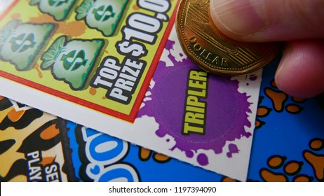 Coquitlam BC Canada - October 05, 2018 : Woman scratching lottery ticket. The British Columbia Lottery Corporation has provided government sanctioned lottery games in British Columbia since 1985.