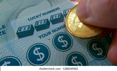 Coquitlam, BC, Canada - October 05, 2018 : Close up of woman scratching lottery ticket. The BC Lottery Corporation has provided government sanctioned lottery games in BC since 1985.