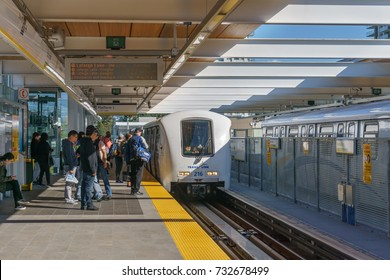 Coquitlam, BC, Canada - October 2017: A train on the Skytrain driverless public transport system about to enter the platform with people waiting at Burquitlam Station of new Evergreen line.