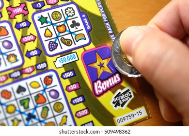 Coquitlam BC Canada - October 31, 2016 : Close up man scratching lottery ticket on bonus section.  The BC Lottery Corporation has provided government sanctioned lottery games in BC since 1985.