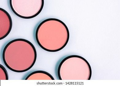 Coral blush and powder on a pastel blue background. Beautiful colorful beauty template. Place for text. Copy space. For advertisement. Trending shades. Living. Makeup. Cosmetic products.