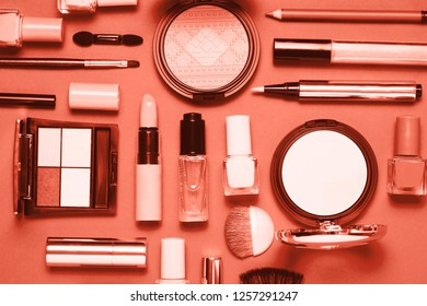 Coral colored Decorative cosmetic and nail polishes set on coral background. Minimalism cosmetics style. Top view, flat lay. Creative fashion beauty concept of color of the year 2019.