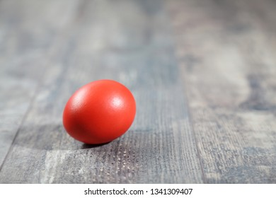 Coral Easter egg on a wooden table, closeup shot