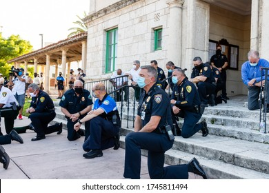 Coral Gables, Florida - May 30, 2020: Police kneeling along side out of view protesters during protest for George Floyd