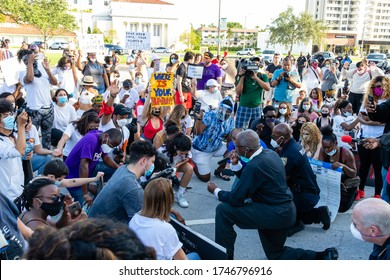 Coral Gables, Florida - May 30, 2020: City police kneeling with protesters in prayer