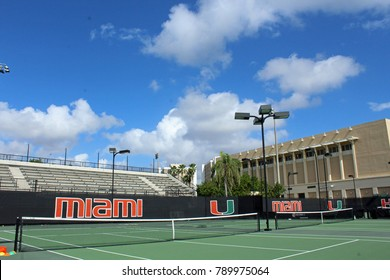 Coral Gables FL/USA: Nov 30, 2017 –University of Miami logo, bleachers and tennis courts at Neil Schiff Tennis Center in Coral Gables FL. The Herbert Wellness Center building is in background.