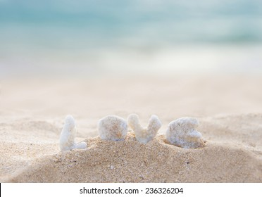 coral letters spelling the word love on the beach in hawaii