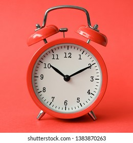 Coral old alarm clock on red background concept