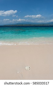 Coral and outrigger on the white sands and crystal clear blue waters of Gili Meno island, Indonesia