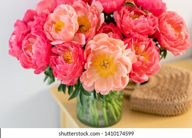 Coral peonies in a glass vase and wicker bag on wooden table.. Beautiful peony flower for catalog or online store. Floral shop concept . Beautiful fresh cut bouquet. Flowers delivery. Copy space