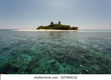Coral reefs easily viewed surrounding small tropical island
