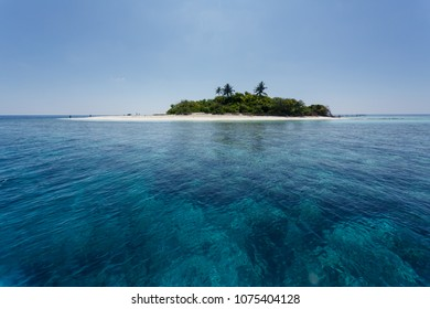 Coral reefs surrounding small tropical Pacific island